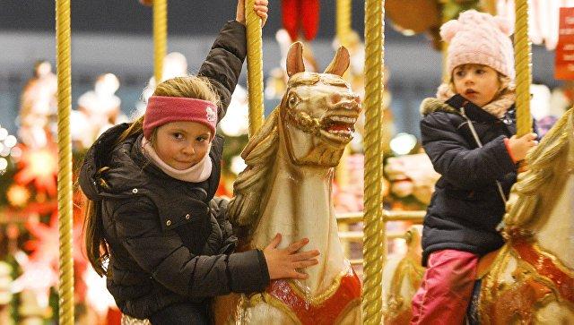 Дети на карусели во время открытия старейшей Рождественской ярмарки Штрицельмаркт в Дрездене