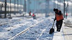 Рабочий очищает железнодорожный путь. Архивное фото