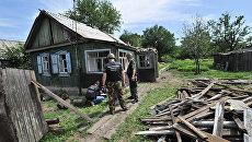 Сотрудники правоохранительных органов работают на месте попадания одного из фугасных снарядов в городе Донецке Ростовской области со стороны украинской территории. Июль 2014 года