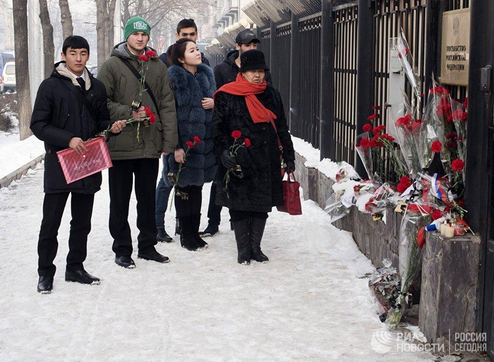 Жители Бишкека приносят цветы к посольству России в память о погибших при крушении самолета Ту-154