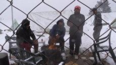 Беженцы грелись у костра в занесенном снегом лагере мигрантов в Салониках