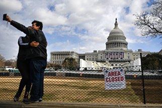Люди фотографируются на фоне Капитолия в Вашингтоне