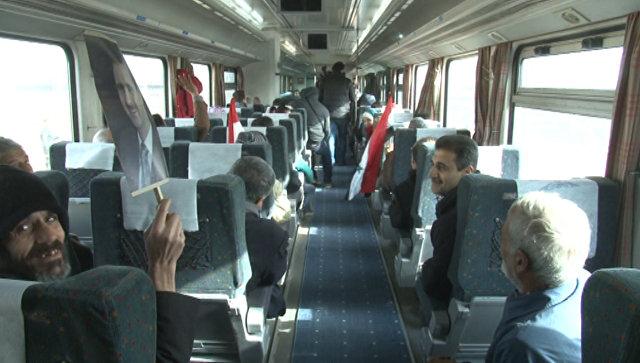 Сирийцы с портретами Асада ехали в первом с начала войны поезде через Алеппо
