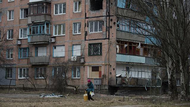 Женщина проходит мимо разрушенного жилого дома в Авдеевке, Украина. Архивное фото