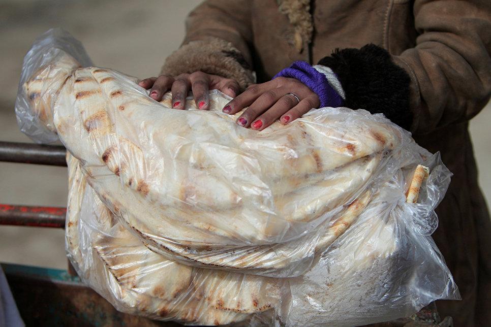 Женщина держит лепешки в городе Алеппо