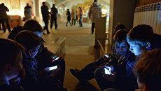 Дети играют в мобильные телефоны в Успенском соборе в Омске