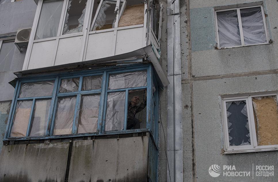 Мужчина заделывает балкон пленкой в Киевском районе Донецка