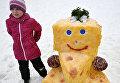 Юная участница возле фигуры из снега во время Арт-битвы Снеговиков в Московском Дворце пионеров на Воробьевых горах