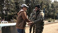 Боец сирийской армии жмет руку боевику из вооруженной оппозиции. Архивное фото