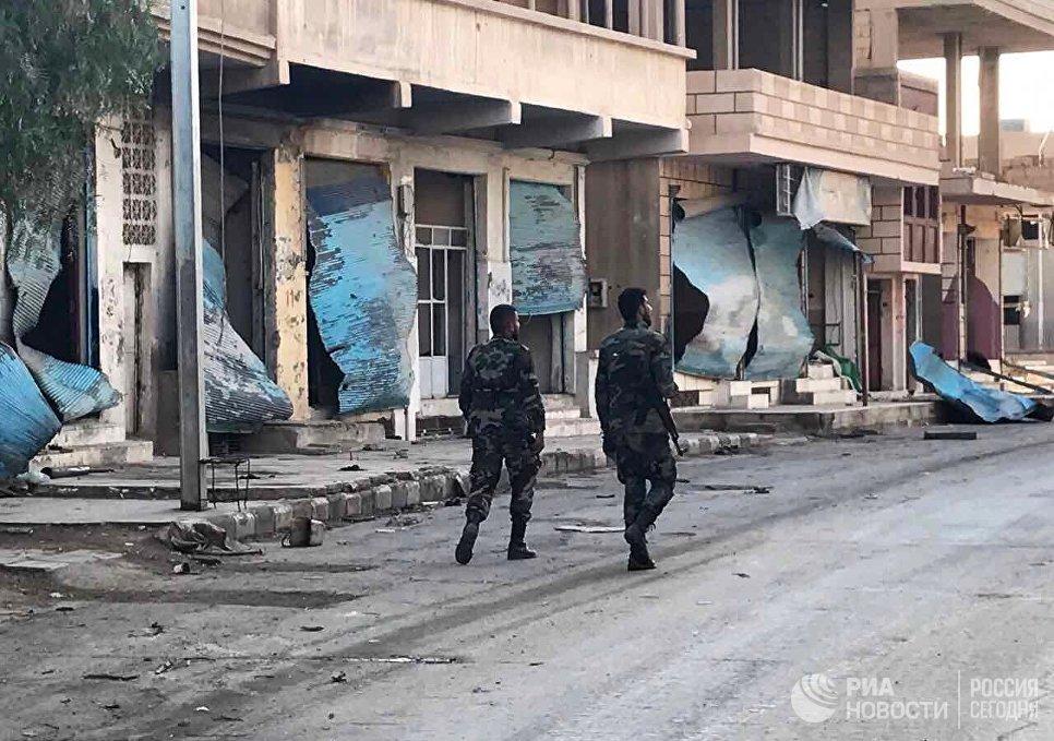 Солдаты у разрушенных в результате боевых действий домов в жилой части города Пальмира в сирийской провинции Хомс