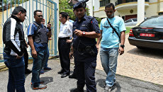 Советник-посланник КНДР Ким Ю Сон и сотрудники полиции Малайзии у здания посольства КНДР в Куала-Лумпуре