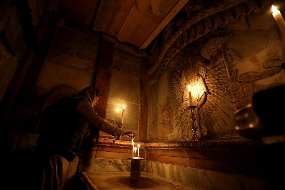 Верующая молится в Кувуклии в храме Гроба Господня