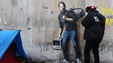 Граффити с изображением Стива Джобса художника Бэнкси на стене лагеря для беженцев в Кале, Франция. Архивное фото