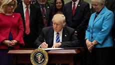 Президент США Дональд Трамп подписывает документы в Белом доме. 27 марта 2017 года