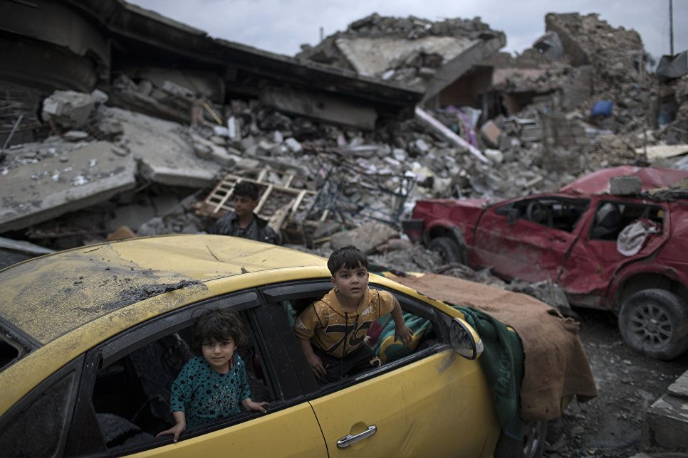Дети играют в поврежденном автомобиле в Мосуле, Ирак