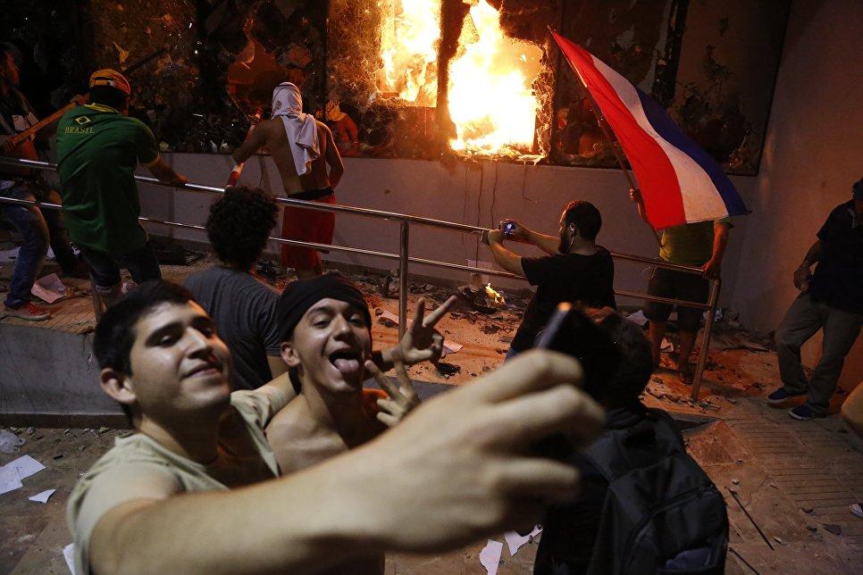 Мужчины фотографируются во время протестов против принятия поправки в конституцию в Асунсьоне, Парагвай