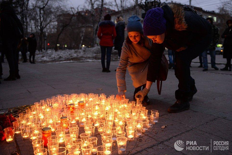 Участники акции Вечер памяти зажигают свечи в Нарымском сквере возле памятника Петру и княгине Февронии в Новосибирске в память о жертвах теракта в Санкт-Петербурге