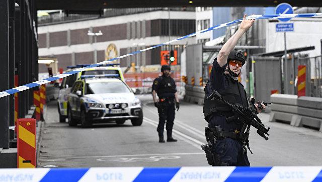 Полицейские в центре Стокгольма после наезда грузовика на людей на улице Дроттнинггатан. 7 апреля 2017
