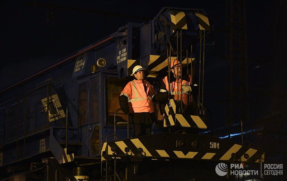 Рабочие на месте столкновения пассажирского поезда и электрички в районе улицы Герасима Курина в Москве