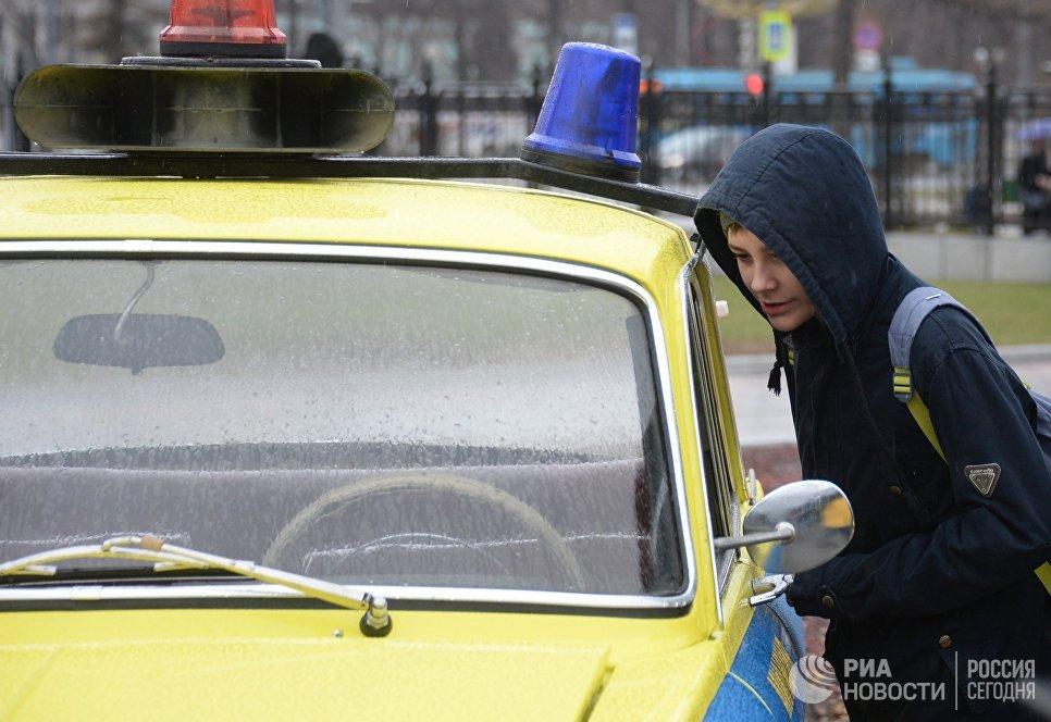 Мальчик у ретро-автомобиля перед стартом автопробега 108 минут в Москве