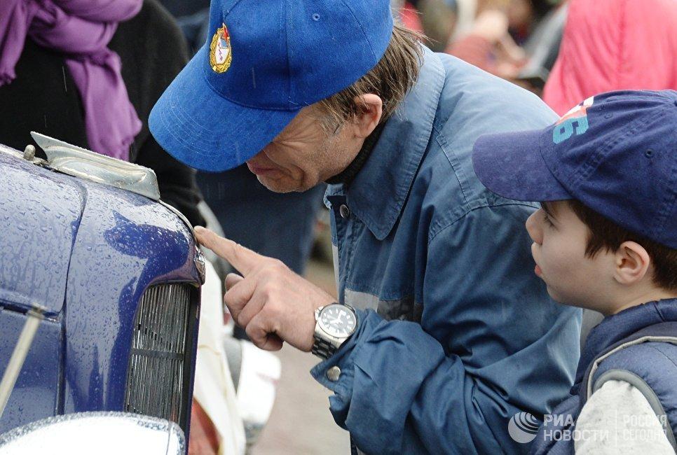 Мужчина с ребенком у автомобиля ГАЗ М1 перед стартом автопробега 108 минут в Москве, приуроченного к 56-й годовщине полета человека в космос
