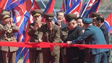 Глава КНДР Ким Чен Ын (первый справа) разрезает красную ленту во время торжественной церемонии открытия нового жилого комплекса на улице Рёмён в Пхеньяне