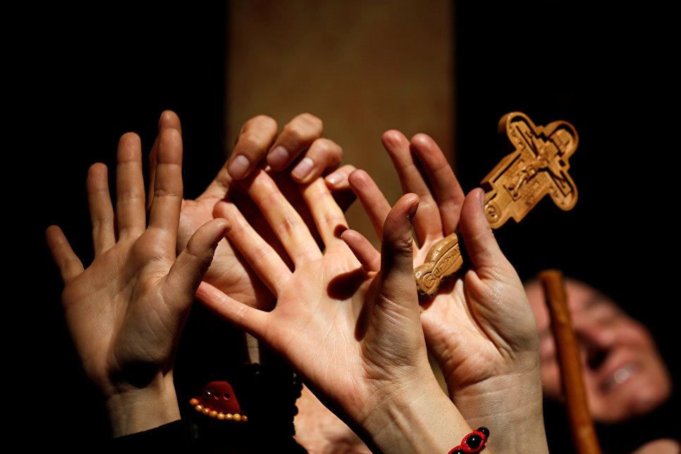 Руки верующих в храме Гроба Господня во время схождения благодатного огня