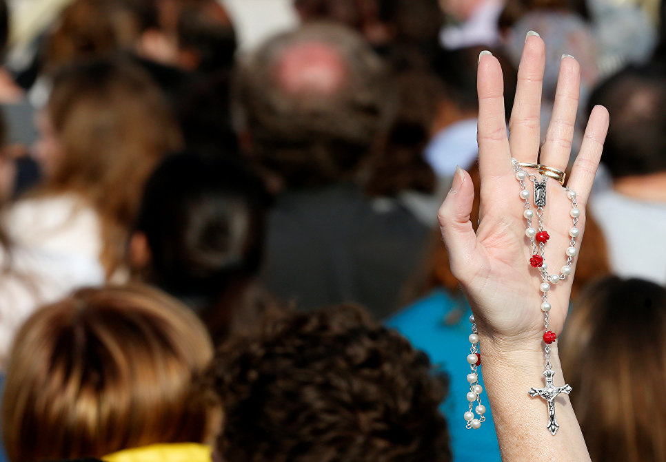 Верующий держит четки на площади Святого Петра в Ватикане на пасхальной мессе