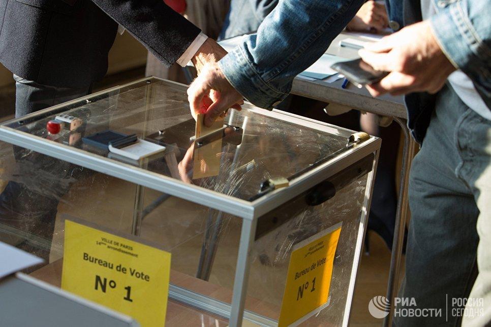 Мужчина голосует на избирательном участке в Париже во время первого тура президентских выборов во Франции
