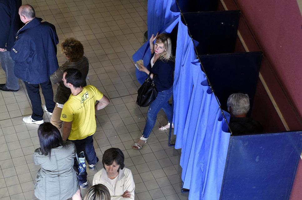 Люди стоят в очереди на избирательном участке в Мартр-Толозан, Франция