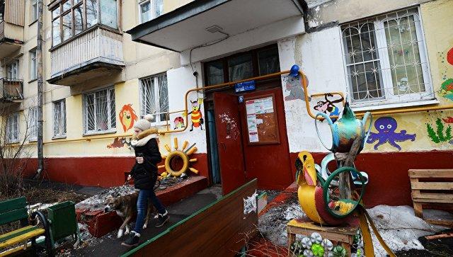 Девушка выходит с собакой из подъезда пятиэтажного жилого дома в районе Измайлово в Москве. Архивное фото
