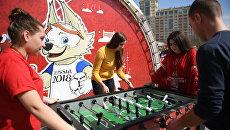 Молодые люди играют в настольный футбол на церемонии открытия Парка Кубка Конфедераций 2017