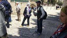 Мусульманин раздает пособия об исламе у церкви Успения Пресвятой Богородицы в Иерусалиме
