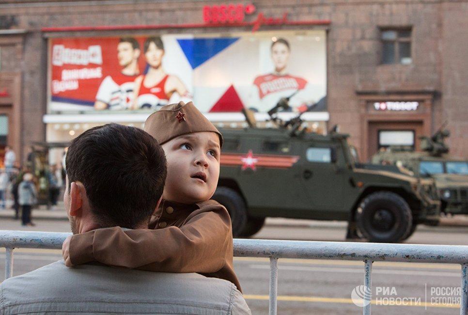 Мужчина с ребенком во время прохода военной техники по Тверской улице перед репетицией парада Победы на Красной площадии