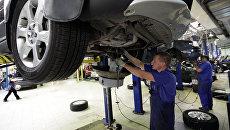 Сотрудник цеха слесарного ремонта проводит замену масла в двигателе автомобиля. Архивное фото