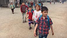 Дети покидают школу после окончания учебного дня в лагере для беженцев. Архивное фото