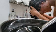 Девушка моет голову нагретой водой во время сезонного отключения горячей воды в Москве