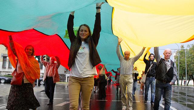 Жители Литвы несут флаг своей страны во время празднования 25-летней годовщины Балтийской цепи