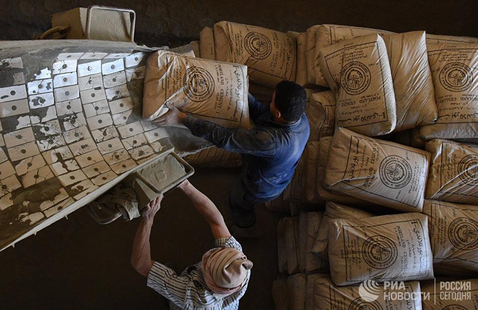 Отгрузка цемента в машину на цементном заводе в пригороде сирийского города Тартуса