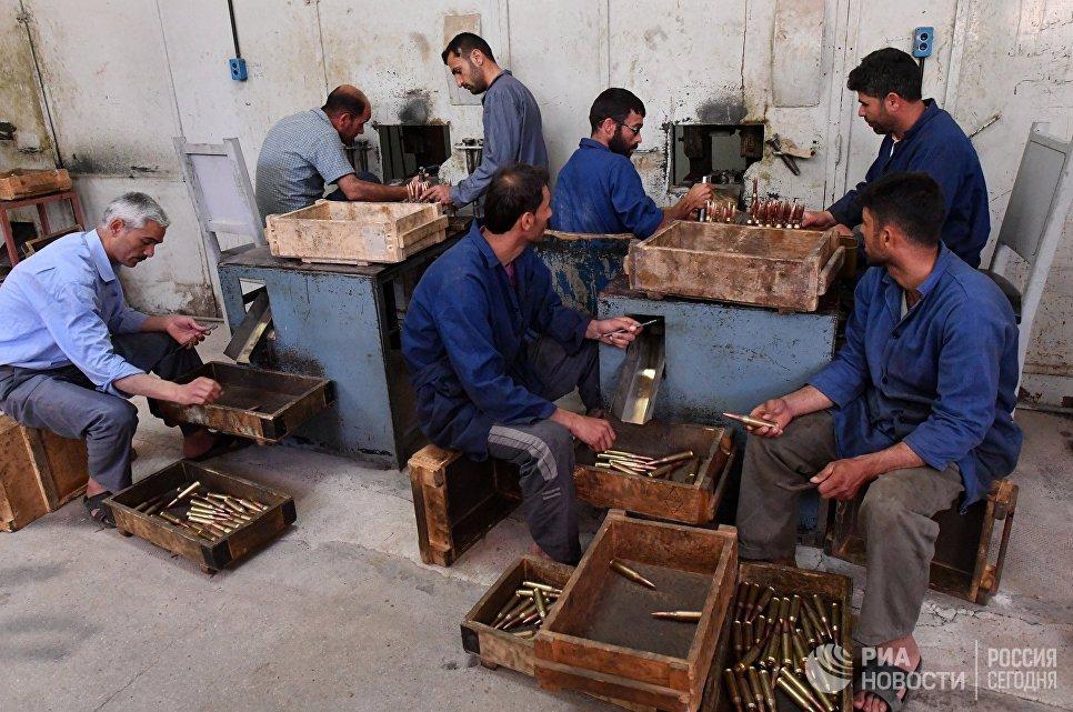 Рабочие в одном из цехов военного завода по изготовлению патронов в пригороде сирийского города Хама