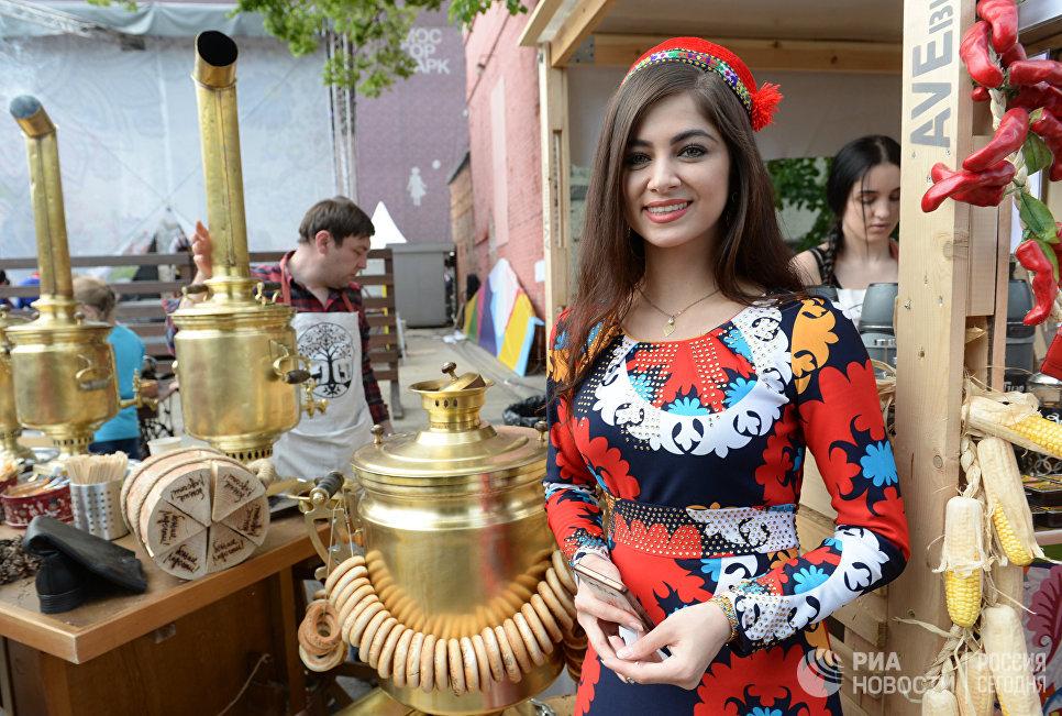 Девушка в национальном костюме встречает гостей на празднике русского гостеприимства СамоварФест в саду Эрмитаж. 12 июня 2017