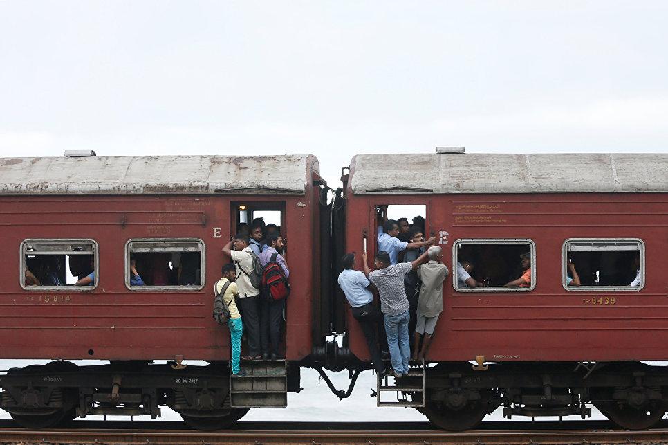 Люди едут на работу в поезде в Коломбо, Шри-Ланка. 14 июня 2017