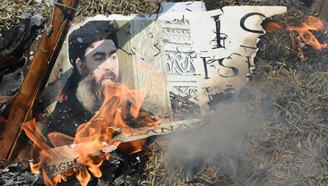 Горящая фотография лидера Исламского государства Абу Бакра аль-Багдади. Архивное фото