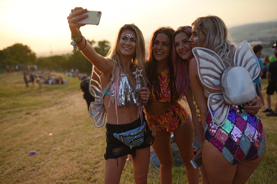 Девушки фотографируются во время музыкального фестиваля Гластонбери в Великобритании