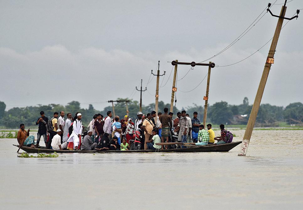 Жители деревни используют лодку, чтобы пересечь затопленную дорогу в деревне штата Ассам, Индия. 4 июля 2017