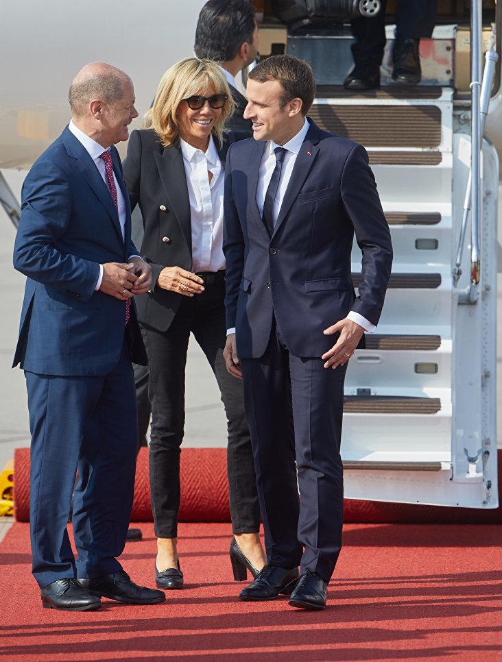 Мэр Гамбурга Олаф Шольц приветствует президента Франции Эммануэля Макрона и его супругу Брижит Тронье в аэропорту Гамбурга