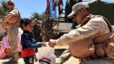 Военнослужащие российского центра по примирению враждующих сторон раздают гуманитарную помощь в сирийской провинции Кунейтра