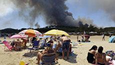 Вид на лесные пожары с пляжа  Ле-Лаванду в регионе Лазурный берег во Франции. 26 июля 2017