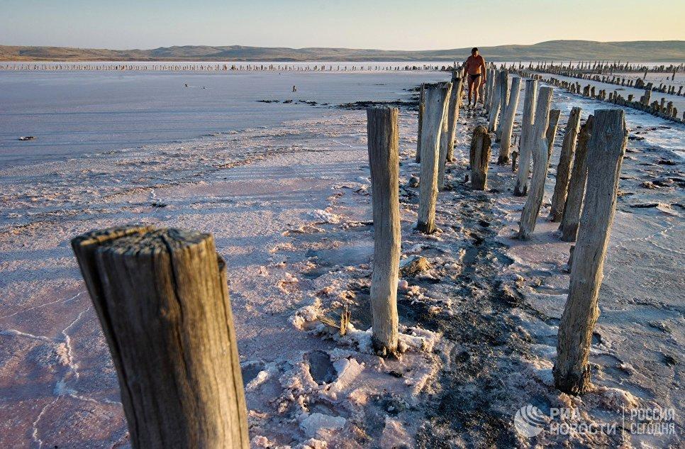 Отдыхающие набирают розовую соль на Чокракском озере в Крыму