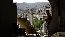 Мужчина смотрит на руины в окрестностях Дамаска. Архивное фото
